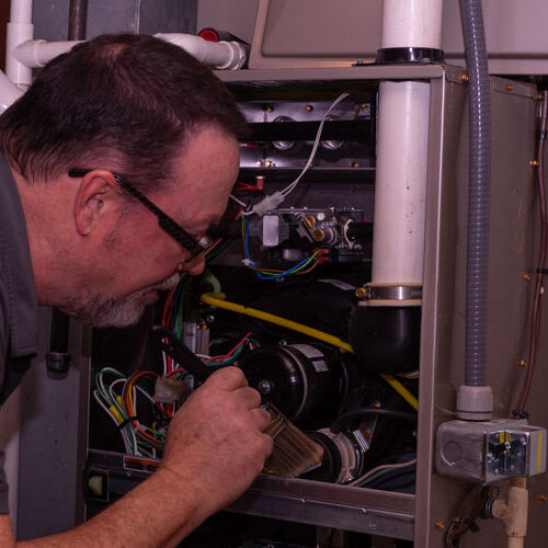 A Technician Inspects a Gas Furnace.