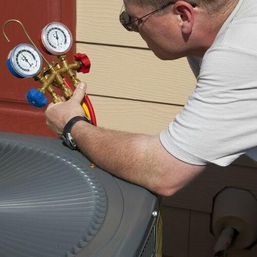 An HVAC Technician Checks and Air Conditioner.